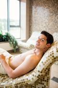 Handsome man relaxing in thermal suite - stock photo