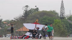 Men preparing kite for lauch,Sanur,Bali,Indonesia Stock Footage