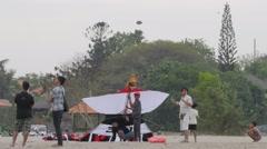 Men lauching kite with long tail,Sanur,Bali,Indonesia Stock Footage