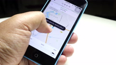 A UBER user looking for a ride using the UBER app on his smartphone. - stock footage