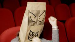 Breadbag face movie theater angry bitter Stock Footage