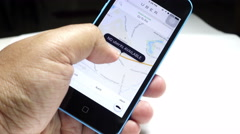 A UBER user looking for a ride using the UBER app on his smartphone. Stock Footage