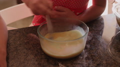 Close up of little girls mixing cookie ingredients in seperate bowls - stock footage