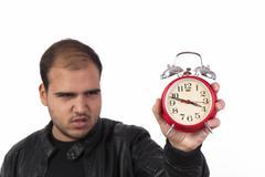 Young man with red alarm clock Stock Photos