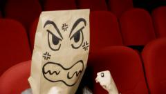 Breadbag face movie theater angry furious Stock Footage