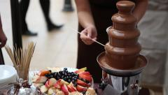 Chocolate fountain and fruit at a party - stock footage
