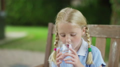 4K Portrait of happy little girl drinking glass of water outdoors in the garden - stock footage