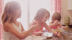 Little girls mixing cookie ingredients in seperate bowls Stock Footage