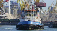 Close up of tug assisting cargo ship in port harbor Stock Footage