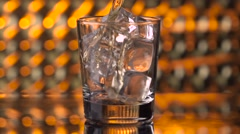 Pouring whiskey drink into glass with ice over bokeh background Stock Footage