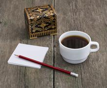 Casket, coffee in a white cup and paper with a pencil, a still life on an old Stock Photos