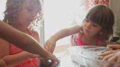 A little girl steals chocolate chips while helping her mom and sisters bake Stock Footage