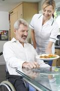 Carer Serving Meal To Man In Wheelchair At Home - stock photo