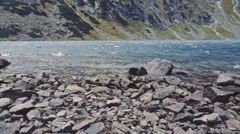 Camera flying to the lake shore in high mountings. Stabilized Slow-Mo, POV. Stock Footage