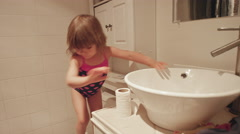 A little girl drying her hands in the bathroom and then running out Stock Footage