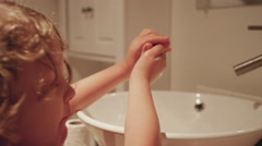 A little girl washing her hands with a slippery bar of soap - stock footage