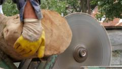 Worker at electric circular saw scraping logs, firewood for heating, close up. - stock footage