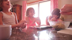 Three little girls helping their mother put cookie dough on a tray Stock Footage