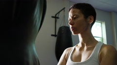 Stock Video Footage of 4K Portrait of serious female martial artist or boxer standing beside punch bag