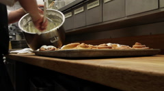 Baker spreading frosting on sweet rolls - stock footage