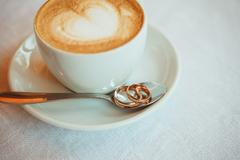 Cup of coffee, wedding rings on table Stock Photos