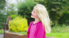 4K Portrait of happy smiling little girl standing outdoors in the garden Stock Footage