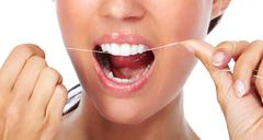 Woman teeth with dental floss. - stock photo