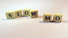 "Slow motion of scrabble tiles falling on tiles spelled ""slow mo"" on a white back Stock Footage"