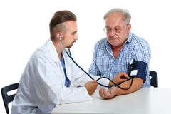 Doctor checking patient blood pressure. - stock photo