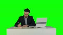 Human hand writing on a paper with laptop on a Green Screen - stock footage