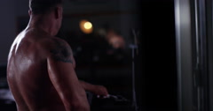 A shirtless man working out at the gym in slow motion. Shot on RED Epic. Stock Footage