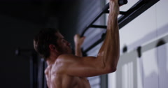 A male muscular athlete performing pull ups on a bar in a industrial looking gym Stock Footage