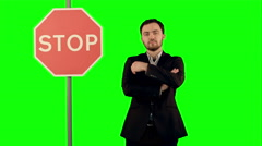 Businessman standing near a stop sign on laptop on a Green Screen, Chroma Key Stock Footage