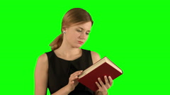 Young beautiful girl reading a book on laptop on a Green Screen, Chroma Key Stock Footage