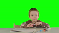A son drawing at the table at home on a Green Screen Stock Footage