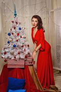 Girl in red dress puts gifts near Christmas tree. - stock photo