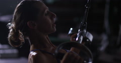 An attractive woman training with weight-lifting training machine. Stock Footage