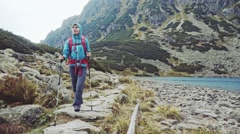 Hiker woman hiking with backpack in high mountains. Stabilized Slow Motion. Stock Footage
