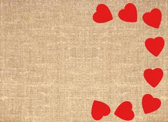 Border frame of red hearts on sack canvas burlap background texture Stock Photos