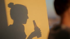 Shadow silhouette of a woman drinking from beer bottle Stock Footage