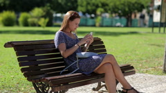 Young beautiful woman make selfy holding mobile phone in hand and sitting on the Stock Footage