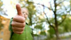 8 years old child hands showing thumbs up while playing in urban park Stock Footage