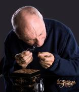 Senior jeweler  looking at jewelry Stock Photos