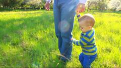 1 year and 5 month old baby making first steps holding hand of his father Stock Footage