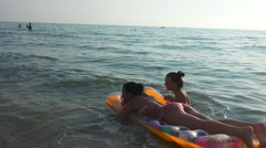 4k Two friends having fun  swimming on inflatable mattress at the beach sunse Stock Footage