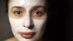 Young girl with a face pack on her face looking at the camera Stock Footage