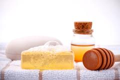 Herbal spa soap bar on white bath towel with honey isolate on white backgroun - stock photo