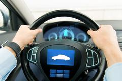 Stock Photo of close up of man driving car with icon on computer