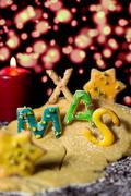 Cookie letters, cookie dough, a candle and icing sugar, wort xmas you in fron - stock photo