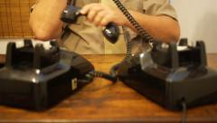 Office clerk - man answers two old telephones at the same time. Stock Footage